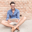 Seated casual man with a tablet pad smiling  — Stockfoto #52425197