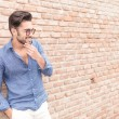 Smiling casual man near brick wall wondering about something — Stock Photo #52425229
