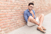 Man looking pensive while sitting on the sidewalk — Stock Photo