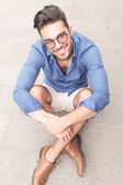 Smiling young casual man with glasses sitting on the sidewalk — Stock Photo