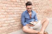 Casual student reading a book while seated  — Stock Photo