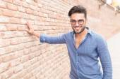 Casual man stands with hand on brick wall — Stock Photo
