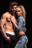 Sexy blonde woman leaning on her topless boyfriend — Stock Photo