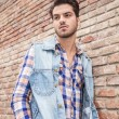 Young casual man leaning on a brick wall — Stock Photo #53339947