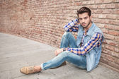 Handsome man resting on the sidewalk, leaning against a wall — Stockfoto