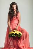 Seated  woman in red dress  holding flower basket and smiles — Stock Photo
