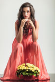 Sexy seated woman in red dress is thinking near flowers — Stock Photo