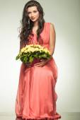 Woman in red dress holding yellow flowers basket and sits — Stock Photo