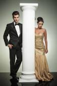 Attractive elegant couple posing near column in studio — Stockfoto
