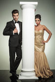 Formal man and woman in evening clothes near column — Stockfoto