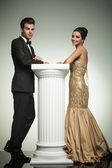 Happy elegant couple leaning ona column — Stockfoto