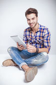 Happy young man holding a tablet pad computer — Stock Photo
