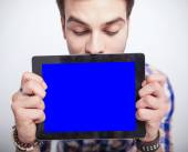 Young man looking down while holding a tablet pad computer  — Stockfoto