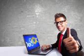 Satisfied business man working on laptop and making ok sign — Stock Photo