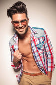 Smiling fashion man pulling his shirt — Stock Photo