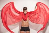 Young naked man fluttering a red textile — Stock Photo