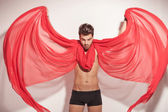 Young naked man fluttering a red textile — 图库照片