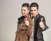 Fashion couple smiling and showing the thumbs up gesture. — Stock Photo