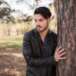 Young fashion man holding his hand on a tree. — Stock Photo #58759139