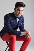 Happy young fashion man sitting on a stool — Stock Photo
