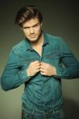 Sexy young fashion man unbuttoning his jeans shirt  — Stock Photo