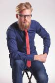 Handsome young fashion man sitting on a stool while — Stock Photo