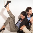 Happy fashion couple sitting together on the floor — Stock Photo #63262497