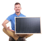 Young seated man presents blank blackboard  — Stock Photo