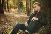 Young casual man leaning on a tree — Stock Photo
