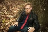 Blond beard fashion man sitting near a tree — Foto de Stock