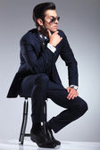Young business man sitting on a stool, thinking — Foto de Stock