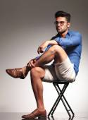 Smart casual young man sitting on a stool — Stock Photo