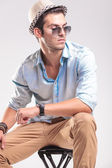 Attractive fashion man resting on a stool — Stock Photo