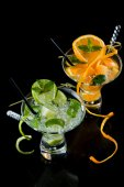 Fresh Orange and lime Mojito over black  background — Stock Photo