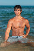 Portrait of a handsome young muscular man in swimwear — Stock Photo