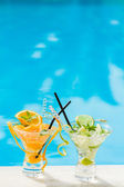 Orange and lime Mojito by the swimming pool — Stock Photo