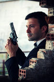 Hitman in tux holding a gun — Stock Photo