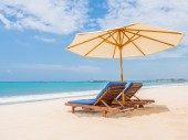Relaxing couch chairs with parasol on white sandy Beach — Stock Photo