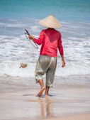 Lone fisherman on beach in the morning — Stock Photo