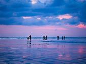 Silhouettes of people at sunset on the beach of Kuta Bali I — Stock Photo
