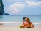 Woman on the beach in Thailand using her tablet — 图库照片