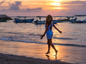 Woman on the beach in Bali Indonesia holding her sandals sunset — Stock Photo