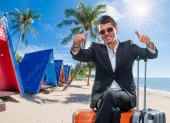 Business man with suitcases at tropical resort — Stock Photo