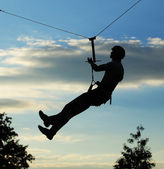 Silhouette of alpinist hang on rope — Stock Photo