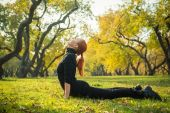 Woman doing yoga in autumn park — Stock Photo