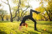 Woman doing yoga in autumn park — Stock Photo