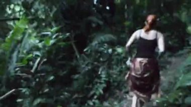 Young woman running thorough jungle — Stock Video