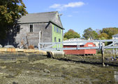 Wood shed by harbor in low tide — Stock Photo
