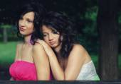 Two beautiful elegant girls sitting in the park — Stock Photo