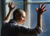 Bald woman suffering from cancer leaning on the hospital window — Stock Photo